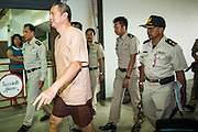 """23 JANUARY 2013 - BANGKOK, THAILAND:  SOMYOT PRUESAKASEMUK walks into Bangkok Criminal Court followed by court security Wednesday. Somyot was sentenced to 11 years imprisonment Wednesday for violations of Thailand's """"Lese Majeste"""" laws. He was arrested on April 30, 2011, and charged under article 112 of Thailand's penal code, which states that """"whoever defames, insults or threatens the King, the Queen, the Heir-apparent or the Regent, shall be punished with imprisonment of three to fifteen years"""" after the magazine he edited, """"Red Power"""" (later changed to """"The Voice of Thaksin"""") published two articles by Jit Pollachan, the pseudonym of Jakrapob Penkair, the exiled former spokesman of exiled fugitive former Prime Minister Thaksin Shinawatra. Jakrapob, now living in Cambodia, has never been charged with any crime for what he wrote.      PHOTO BY JACK KURTZ"""