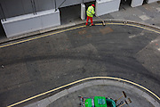 Aerial view of a corporation of London contract street sweeper brushes litter in the gutter of a City street.