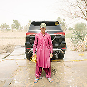 Khan Mohammed Baluch, an employee of a car wash is drenched in water.
