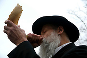 The local Tokea (Blaster) Rabbi Kahn blowing a Shofar for Rosh Hashanah to mark the start of the new year in Stamford Hill. The Shofar is usually made from a Rams horn and is one of the earliest wind instruments known to man. It is considered one of the commandments to hear a Shofar on Rosh Hashanah.