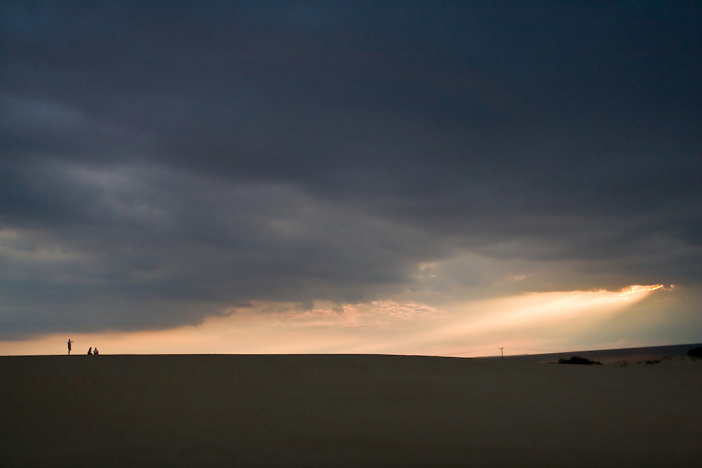 Sunlight breaks through storm clouds over the Outer Banks as three figures watch.