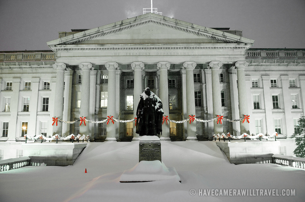 The US Treasury Building in a snowstorm at night decked out with holidy decorations