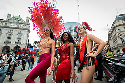 © Licensed to London News Pictures. 29/08/2021. LONDON, UK.  Samba dancers in colourful costumes take part in a flashmob in Piccadilly Circus organised by fashion brand RioPump GymWear.  The August Bank Holiday weekend would normally see tens of thousands of people watching events at the Notting Hill Carnival, including samba dancers, but for the second year running, the carnival has been cancelled due to Covid-19 concerns.  Photo credit: Stephen Chung/LNP