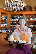Cheesemonger Luan Schooler in her store, Foster and Dobbs, in a neighborhood in NE Portland, Oregon.  She's holding a variety of cheeses that the store carries.