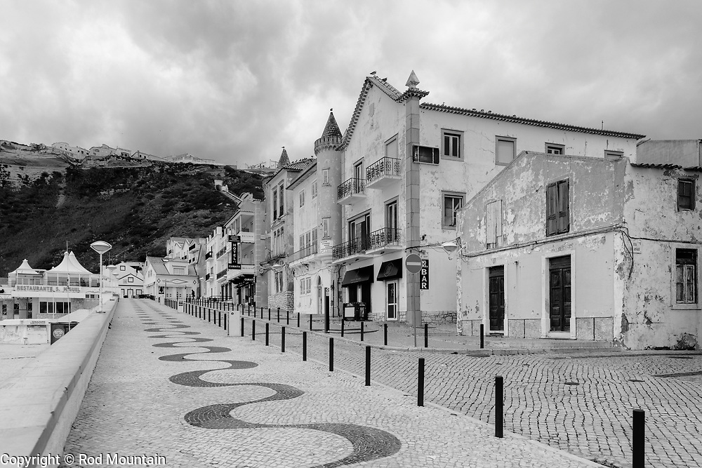 Nazaré, Portugal - February 13, 2018 - Near the Beach in Nazaré 01 - A  cobblestone walkway winds up toward the end of the street near the beach in Nazare. Portuguese pavement (calçada portuguesa) is distinctive and often takes on a form of art which can be found throughout Portugal, Brazil and Macau. Hotel Cubata and Restaurante São Miguel are seen in the background. <br /> <br /> Image: © Rod Mountain<br /> <br /> http://www.rodmountain.com<br /> http://bit.ly/Nazaré_bw<br /> http://bit.ly/Nazare_Portugal<br /> <br /> Nikon D800 / Nikkor Lens<br /> @nikoncanada #NikonCA<br /> @NikonUSA<br /> @nikoneurope #NikonEurope<br /> <br /> https://www.visitportugal.com/en<br /> @visitportugal <br /> <br /> https://en.wikipedia.org/wiki/Nazaré,_Portugal<br /> http://www.cm-nazare.pt/en<br /> @municipiodanazare @cmnazare @CMNazareMata <br /> <br /> http://www.hotelcubata.com<br /> @ACubataHotel<br /> http://www.s-miguel.com<br /> @smiguelnazare<br /> <br /> https://en.wikipedia.org/wiki/Portuguese_pavement<br /> https://en.wikipedia.org/wiki/Portugal<br /> <br /> #iglobal_photographers #tourism #worldcaptures #justgoshoot #TheGlobeWanderer #everydayportugal #ignanttravel #travels <br /> <br /> #stayandwander #explore #bwsquare #bnw_captures #bnw_universe #bwmasters #blacknwhitepic #neverstopexploring#featuremeinstagood #ourstreets <br /> <br /> #blackandwhite #blackandwhitephotography<br /> #neverstopexploring #blackandwhite #blacknwhitepic #bnw_universe #insta_bw #bnw_demand #bw #bnw
