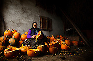 Elderly Romaninan woman cleaning pumpkins