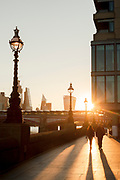 Man and woman walking along Southbank at sunrise, London, England, UK
