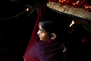 A young girl is joining is joining bracelets with the use of a gas flame inside her home transformed into a small-scale workshop in the slum surrounding Firozabad, renowned as the 'glass city', in  Uttar Pradesh, northern India. Due to extreme poverty, over 20.000 young children are employed to complete the bracelets produced in the industrial units. This area is considered to be one of the highest concentrations of child labour on the planet. Forced to work to support their disadvantaged families, children as young as five are paid between 30-40 Indian Rupees (approx. 0.50 EUR) for eight or more hours of work daily. Most of these children are not able to receive an education and are easily prey of the labour-poverty cycle which has already enslaved their families to a life of exploitation. Children have to sit in crouched positions, use solvents, glues, kerosene and various other dangerous materials while breathing toxic fumes and spending most time of the day in dark, harmful environments. As for India's Child Labour Act of 1986, children under 14 are banned from working in industries deemed 'hazardous' but the rules are widely flouted, and prosecutions, when they happen at all, get bogged down in courts for lengthy periods. A ban on child labour without creating alternative opportunities for the local population is the central problem to the Indian Government's approach to the social issue affecting over 50 million children nationwide.