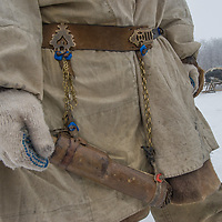 North of the Arctic Circle in Russia, a young, nomadic Komi reindeer herder displays his knife scabbard that hangs from a traditional decorated belt.