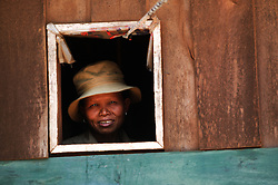 Portrait of woman looking from the window of a wooden building. Near Dakcheung, near Sekong, Lao PDR