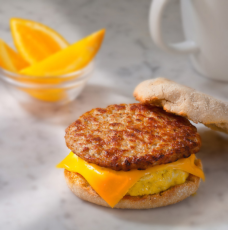 sausage patty with egg and cheese on english muffin,sliced oranges,coffee cup,sitting on a white and grey marble top