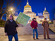 17 DECEMBER 2019 - DES MOINES, IOWA: DIANE JONES, from West Des Moines, left, and others stand on the sidewalk in front of the Iowa State Capitol and call for the impeachment of President Donald Trump. About 300 people came to the Iowa State Capitol in Des Moines in near freezing weather Tuesday evening to call for Trump's impeachment. The rally, and others like it around the US, come on the eve of an impeachment vote in the US House of Representatives.     PHOTO BY JACK KURTZ