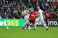 Man Utd's Wayne Rooney is closed down by Swansea's Michu (l) and Jonjo Shelvey (r). Barclays Premier league, Swansea city v Manchester Utd in Swansea, South Wales on Saturday 17th August 2013. pic by Andrew Orchard ,Andrew Orchard sports photography,
