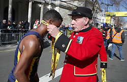 A competitor receives his medal from Chelsea pensioners during the 2019 London Landmarks Half Marathon.
