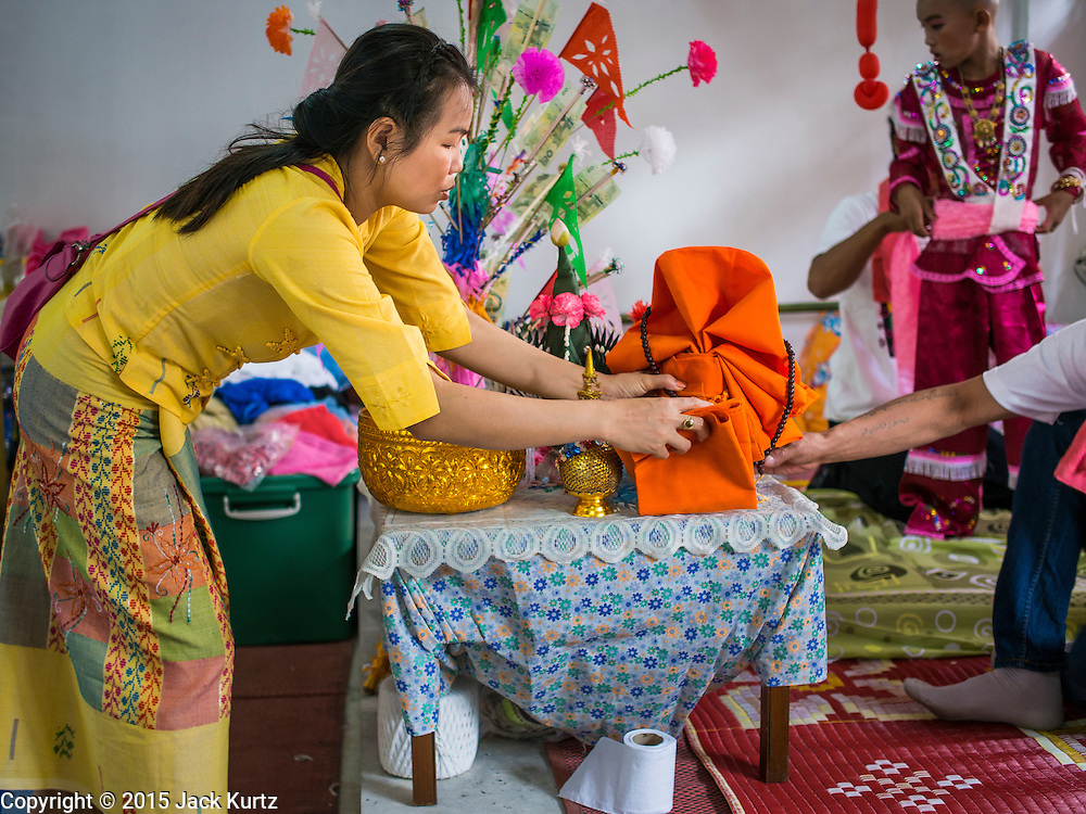 """04 APRIL 2015 - CHIANG MAI, CHIANG MAI, THAILAND: A woman sets up a boy's alter for the Poi Sang Long Festival at Wat Pa Pao in Chiang Mai. The Poi Sang Long Festival (also called Poy Sang Long) is an ordination ceremony for Tai (also and commonly called Shan, though they prefer Tai) boys in the Shan State of Myanmar (Burma) and in Shan communities in western Thailand. Most Tai boys go into the monastery as novice monks at some point between the ages of seven and fourteen. This year seven boys were ordained at the Poi Sang Long ceremony at Wat Pa Pao in Chiang Mai. Poy Song Long is Tai (Shan) for """"Festival of the Jewel (or Crystal) Sons.     PHOTO BY JACK KURTZ"""