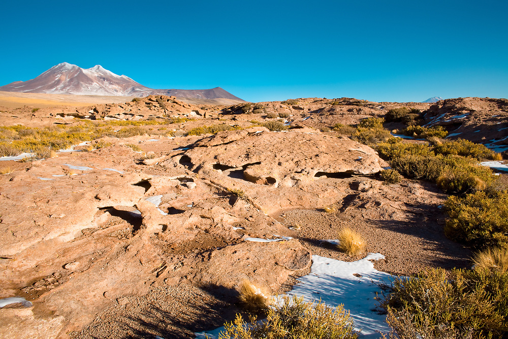 Rock formations of dry lava, with Cerro Miniques (Miniques hill) in the background in the Altiplano (high Andean Plateau), Los Flamencos National Reserve, Atacama desert, Chile, South America