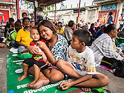 "09 AUGUST 2014 - BANGKOK, THAILAND:  A woman and her children wait for food to be handed out at the Ruby Goddess Shrine in the Dusit section of Bangkok. The seventh month of the Chinese Lunar calendar is called ""Ghost Month"" during which ghosts and spirits, including those of the deceased ancestors, come out from the lower realm. It is common for Chinese people to make merit during the month by burning ""hell money"" and presenting food to the ghosts. At Chinese temples in Thailand, it is also customary to give food to the poorer people in the community.        PHOTO BY JACK KURTZ"