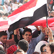 A determined young man fixes his eyes to the camera as he joins with hundreds of others passing a giant Egyptian flag over the crowd in Cairo's Tahrir Square.