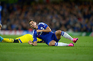 Eden Hazard of Chelsea rolls on the pitch after he is fouled by Nosa Igiebor of Maccabi Tel Aviv. UEFA Champions League group G match, Chelsea v Maccabi Tel Aviv at Stamford Bridge in London on Wednesday 16th September 2015.<br /> pic by John Patrick Fletcher, Andrew Orchard sports photography.