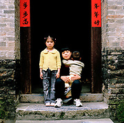 Xu Zhen, 26 and her two children Xu Feng, 5 (daughter) and Yang Chao Heng, 2 (son) from Hunan province, are staying with her mother, Wu Shu Lin, 50, at her home in, Guangxi province. Zhen is six months pregnant with her third child. If the authorities found out, they could force her to have a termination so she will only travel back to her province once the baby is born (its identity will not be linked to her husband's name that way) Many women get around the policy this way...Its over thirty years (1978) since the Mao's Chinese government brought in the One Child Policy in a bid to control the world's biggest, growing population. It has been successful, in controlling growth, but has led to other problems. E.G. a gender in-balance with a projected 30 million to many boys babies; Labour shortages and a lack of care for the elderly.