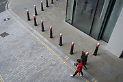 As workers in London largely remain working from home during the Coronavirus pandemic, two figures walk across an urban street landscape of road markings and traffic bollards in the City of London, the capital's financial district, on 4th September 2020, in London, England.