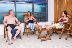 Adults relaxing by the pool side at their sports leisure centre,