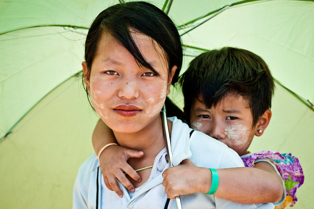 A Naga girl and her sister wearing a typical sunscreen made from a clay paste.