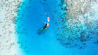 Aerial view of a ship wreck and a boat near Keyodhoo, Vaavu Atoll, Maldives, Indian Ocean with people snorkeling