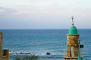 Israel, Jaffa, The turret of El Baher mosque and the Andromeda rock at the entrance to the harbour in the background.