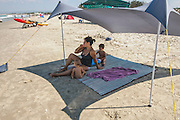 A mother and her two young children vacationing on a beach under a shade tent. Model releases available