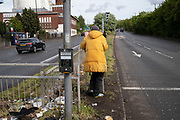 Homeless man on crutches stands beside empty main road waiting for cars to pull up at the lights, which he attempts to speak to and engage with their drivers at Belgrave Middleway near Birmingham Central Mosque in Highgate, the inner city area of Birmingham which is virtually deserted under Coronavirus lockdown on 29th April 2020 in Birmingham, England, United Kingdom. Coronavirus or Covid-19 is a new respiratory illness that has not previously been seen in humans. While much or Europe has been placed into lockdown, the UK government has put in place more stringent rules as part of their long term strategy, and in particular social distancing.
