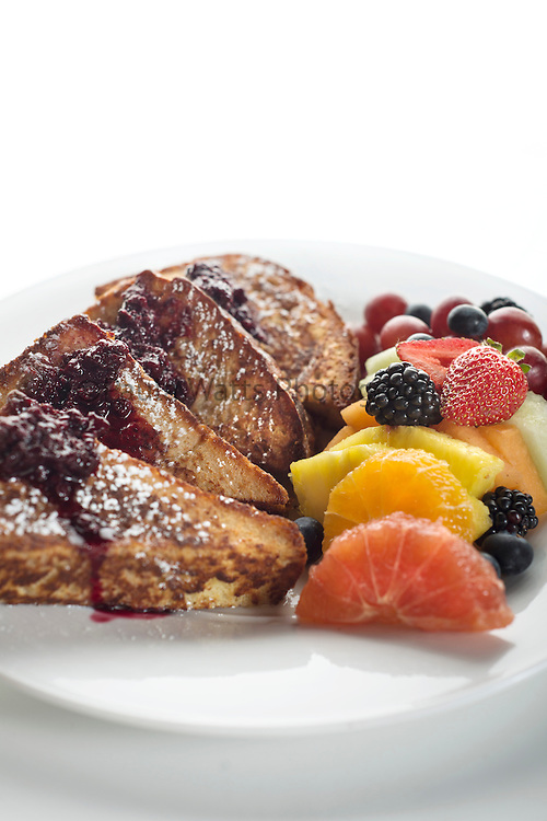 Breakfast french toast with powdered sugar, syrup and fresh fruit