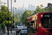 With the London skyline in the far distance, a bus and morning traffic descend Gypsy Hill in Crystal Palace, on 16th June 2021, in London, England.