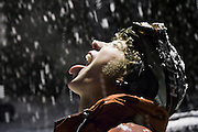 Skier Zach Podell-Eberhardt opens his mouth to the sky hoping to catch falling snowflakes on his tongue during a night snow storm in Whistler Village, British Columbia, Canada.