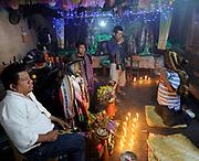 Inside the house of the folk-saint Maximon or San Simon, the evil saint. The effigy of Maximon wears bright scarves and smokes a cigarette. Santiago Atitlan, Republic of Guatemela. 04Mar14