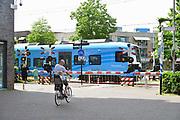 Nederland, Ede, 6-7-2017Een bewaakte spoorwegovergang in het centrum van de stad. De spoorbomen zijn omlaag en de rode lichten knipperen. Foto: Flip Franssen
