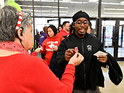 Gordman's manager Cindy Jackson hands a raffle ticket for an oversized Teddy Bear to customer Charles McPherson of O'Fallon, Illinois as he enters the store. Shoppers looking for bargains and discounted items endured a light but steady rain on Thanksgiving Day as they waited for stores to open in Fairview Heights, IL on November 28, 2019.<br />  Photo by Tim Vizer