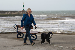 © Licensed to London News Pictures. 19/09/2018. Aberystwyth, UK. A woman walks her dog in Aberystwyth, as  Storm Ali, the first named storm of the UK winter season, gathers strength, promising very high winds and heavy rain for north western parts of the UK. Photo credit: Keith Morris/LNP