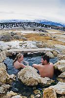 Couple soaks in winter at Travertine Hot Springs, Eastern Sierras, California.