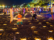 26 DECEMBER 2014 - PATONG, PHUKET, THAILAND: People walk through a field of candles buried in the sand during a memorial service for victims of the 2004 tsunami on Patong Beach in Patong, Phuket. Hundreds of people died in Patong and nearly 5400 people died on Thailand's Andaman during the 2004 Indian Ocean Tsunami that was spawned by an undersea earthquake off the Indonesian coast on Dec 26, 2004. In Thailand, many of the dead were tourists from Europe. More than 250,000 people were killed throughout the region, from Thailand to Kenya. There are memorial services across the Thai Andaman coast this weekend.    PHOTO BY JACK KURTZ