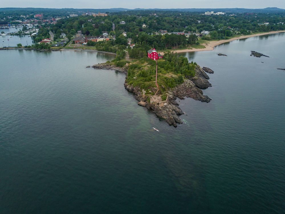 Aerial drone photo of a kayaker and the Marquette Lighthouse in Marquette, Michigan.