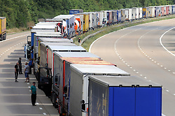 © Licensed to London News Pictures. 30/07/2015<br /> Lorries joining the j9 queue with police supervision. <br /> Lorries stacked up between J8 and J9 M20 (this afternoon 30.07.2015).coast bound.<br /> Traffic misery continues on the M20 with Operation Stack and will most likely remain in place into the weekend.<br /> A 23-mile stretch of the coast-bound carriageway is shut with part of the London-bound side also closed.<br /> <br /> <br /> (Byline:Grant Falvey/LNP)