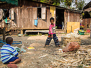 """28 FEBRUARY 2014 - MAE SOT, TAK, THAILAND: Burmese boys play in front of their homes in Mae Sot. Mae Sot, on the Thai-Myanmar (Burma) border, has a very large population of Burmese migrants. Some are refugees who left Myanmar to escape civil unrest and political persecution, others are """"economic refugees"""" who came to Thailand looking for work and better opportunities.    PHOTO BY JACK KURTZ"""