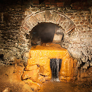 An excavated section of some of the original watercourse plumbing underneath the historic Roman baths in Bath, Somerset, UK.