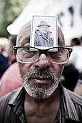Un uomo mostra la foto del padre deceduto durante la manifestazione. Christian Mantuano/OneShot