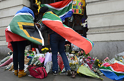 © Licensed to London News Pictures.06/12/2013. London, UK. Members of the public lit candles at the South African Embassy, London to pay tribute to late former South African president Nelson Mandela following his death in Johannesburg.Photo credit : Peter Kollanyi/LNP
