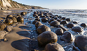 Bowling Ball Beach, Schooner Gulch State Park, south of Point Arena, Mendocino County, California, USA. Pacific Ocean waves have weathered coastal bluffs (steeply tilted beds of Miocene Galloway Formation, Cenozoic Era mudstone) to expose spherical sandstone concretions resting on bowling lanes. Concretions form because minerals of like composition tend to precipitate around a common center. The panorama was stitched from 2 overlapping photos.