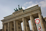 Wide landscape and architecture of the Brandenburg Gate (Brandenburger Tor) in Berlin Mitte. The structure is a former city gate, rebuilt in the late 18th century as a neoclassical triumphal arch, and now one of the most well-known landmarks of Germany. It is located west of the city centre of Berlin at the junction of Unter den Linden and Ebertstraße, immediately west of the Pariser Platz. When the Nazis ascended to power they used the Gate as a party symbol. The Gate only just survived World War II and was one of the damaged structures still standing in the Pariser Platz ruins in 1945 alongside the nearby Reichstag.