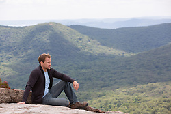 good looking man outdoors on a rock in Bear Mountain, NY
