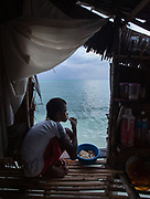 A teenage boy has diner in his bamboo stilt house. On Mantabuan island. On Mantabuan island.